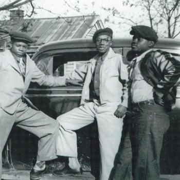 Three residents of Columbia's Ward One neighborhood pose by a car.