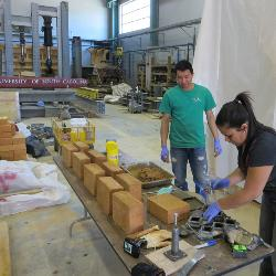 Senior Narong Phal (left) and doctoral candidate Mabel Cuellar work to get the right mix of clay, soil and cement to make stabilized earth masonry.