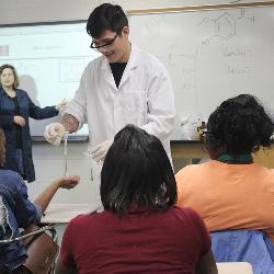 Chemistry professor Linda Shimizu and graduate student Arthur Korous put on a chemistry show for Eau Claire High School students.