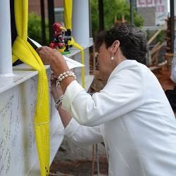 Paula Harper Bethea signs the top beam at the new alumni center construction site..