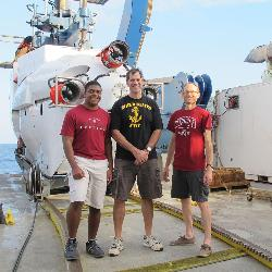Senior Avery Lee, pilot Bruce Strickrott and associate professor Scott White (left to right) were the crew on board the deep-sea submersible Alvin (background left) for a dive that went more than a mile below the surface of the ocean.