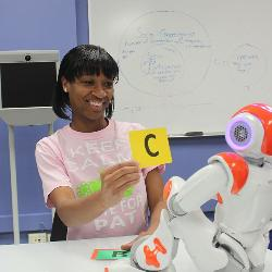 "Karina Liles works here with a robot dubbed Ms. An, which helps tutor fifth-grade students on multiplication skills. The robot can recognize letters held up as answers and offers ""fist-bumps"" for correct responses."