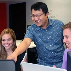 UofSC alumni Andrea Martin, Tong Wu and Tim Duzan work together to solve client software problems at TCube Solutions.