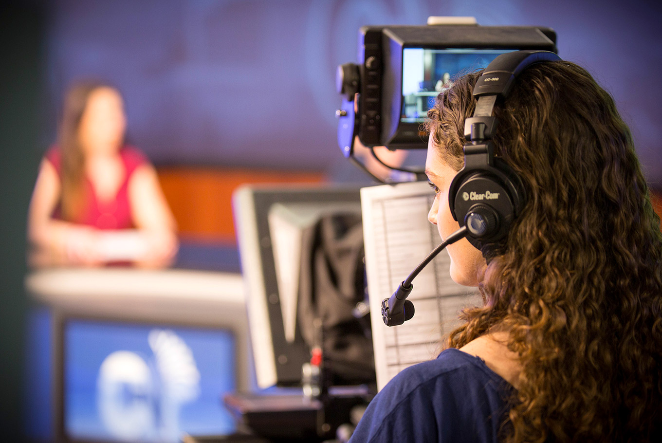Female student works at a TV station with a headset on.