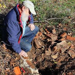 USC archaeologist Chester Depratter examines ruins of wall at the site of Camp Asylum.