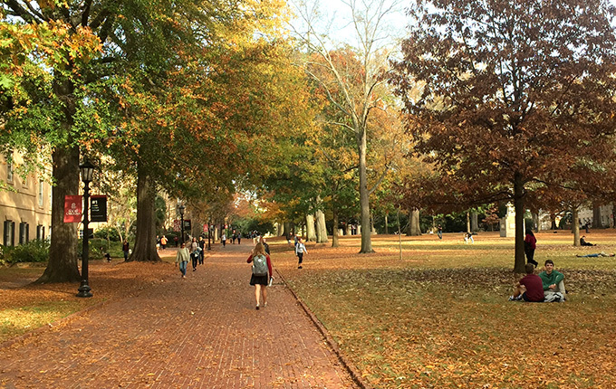 Students walking the brick walkways of the UofSC Horseshoe, surrounded by trees and historic buildings.