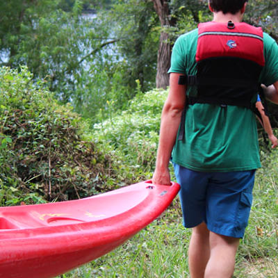 student in a life vest carrying a red kayak