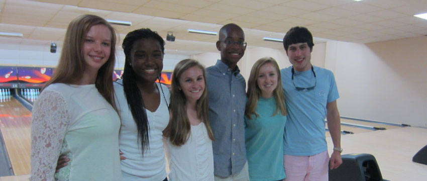 six Carolina Master Scholars standing in front of the bowling lanes