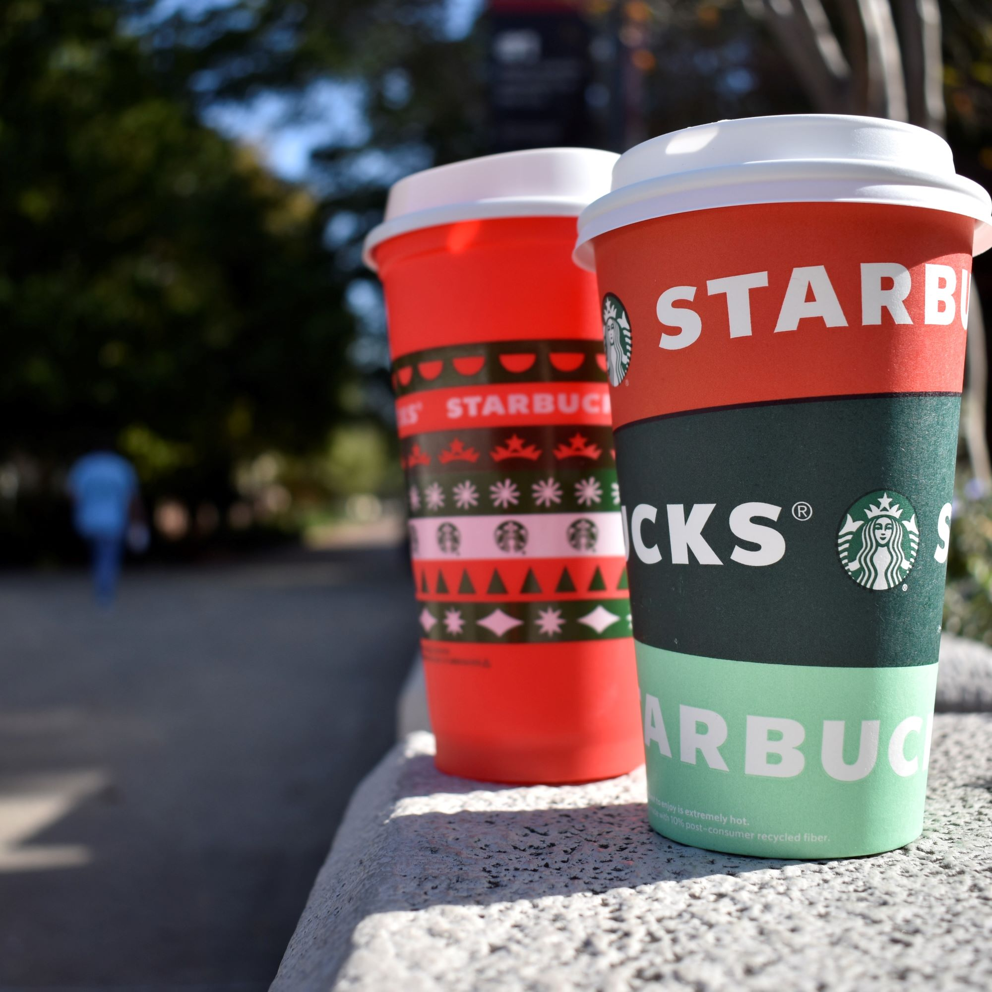 two starbucks cups on a sunny walkway