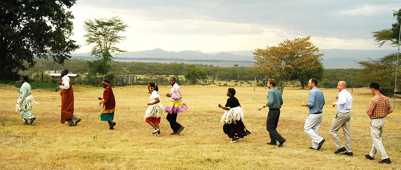 Volunteers and locals dancing in a circle on a field in Kenya. (Courtesy of Peace Corp)