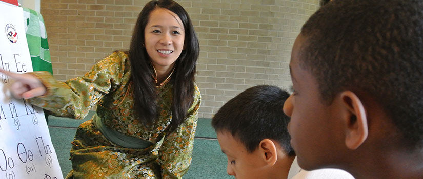 Volunteer teaches foreign alphabet to children at Peace Corp Week. (Courtesy of Peace Corp)