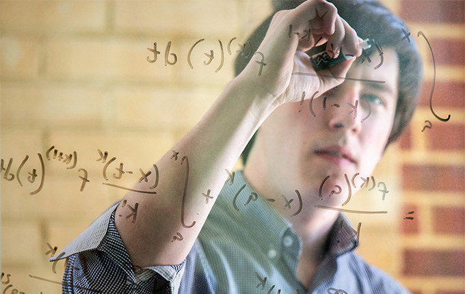 Connor Bain solving an equation on glass