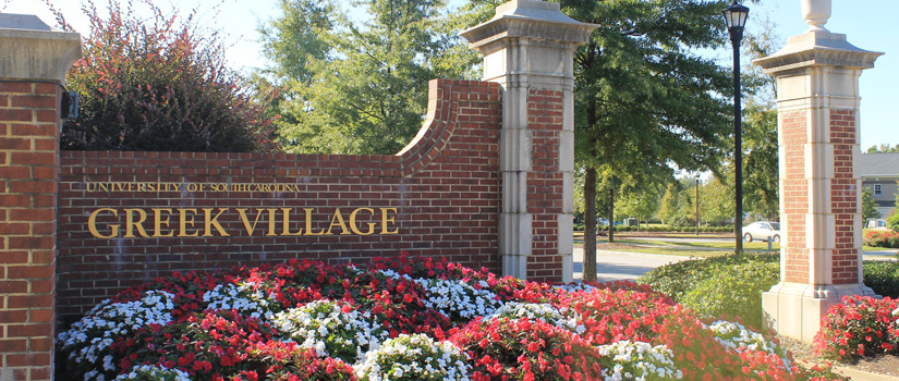 Greek Village entrance with flowers around brick gate