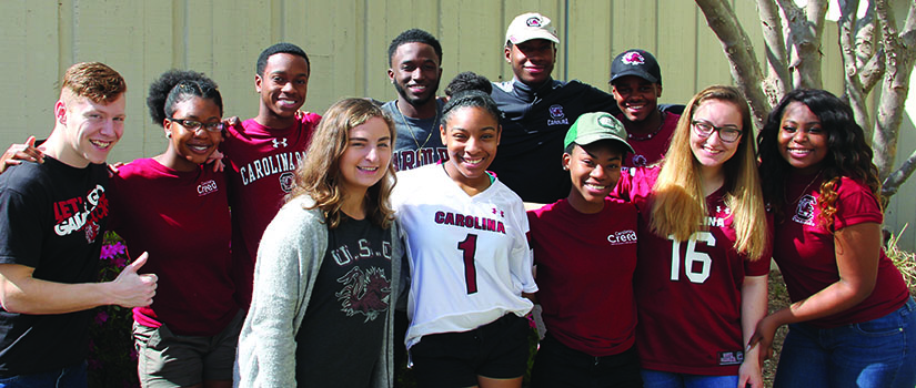 A group of Gamecock Gateway students wear Carolina gear as they pose for the camera.