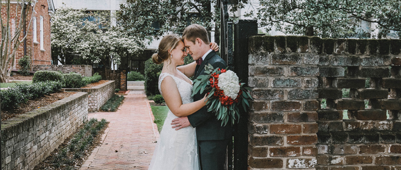 Bride and groom leaning against the brick gates of the garden