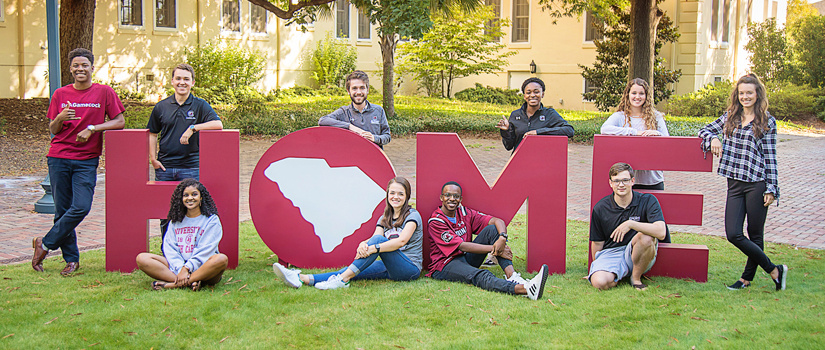 Carolina students surrounding large letters that spell HOME