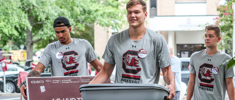 three gentlemen carrying tubs into a residence hall on move in day 2019
