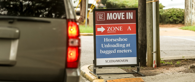 Tail lights of a car as it passes a Move-In sign highlighting parking at the Horseshoe