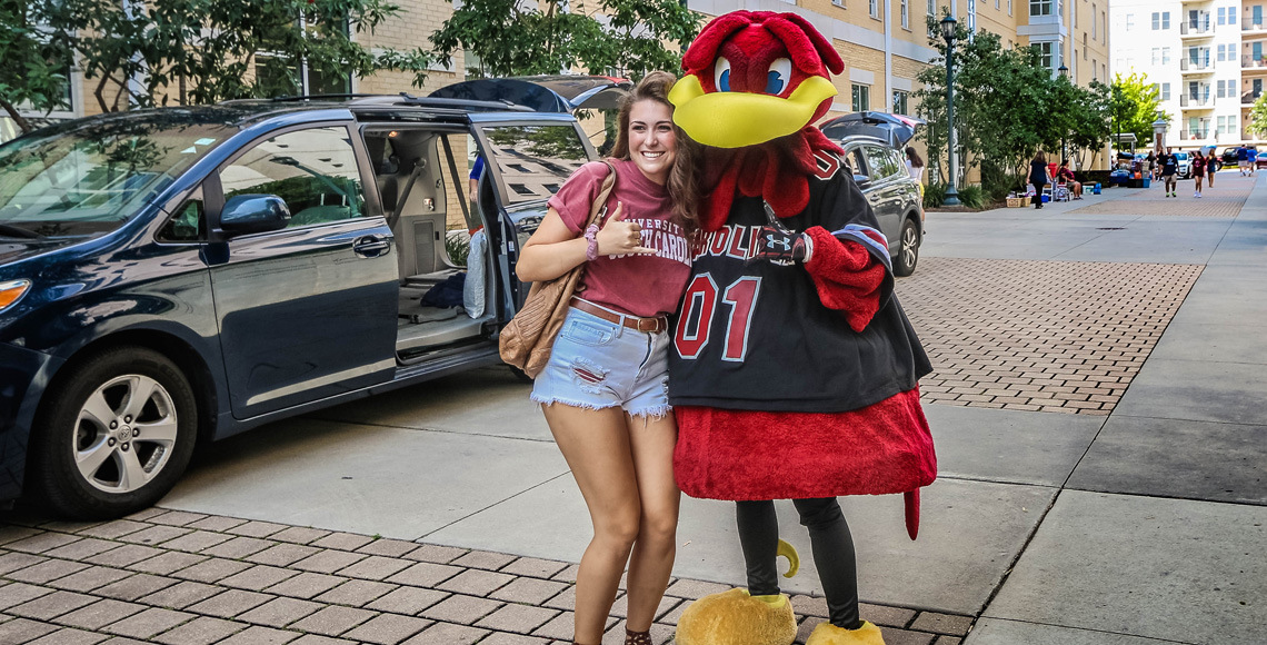 Student posing with cocky on move-in day