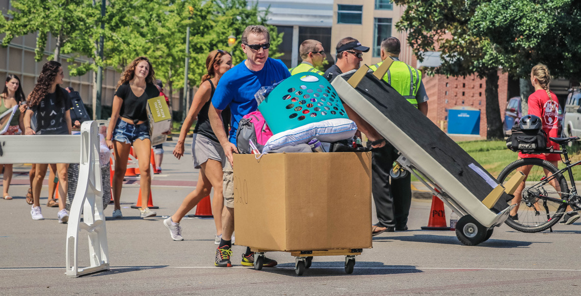 Students with their parents pushing the move-in carts across the road into Patterson Hall on move-in day