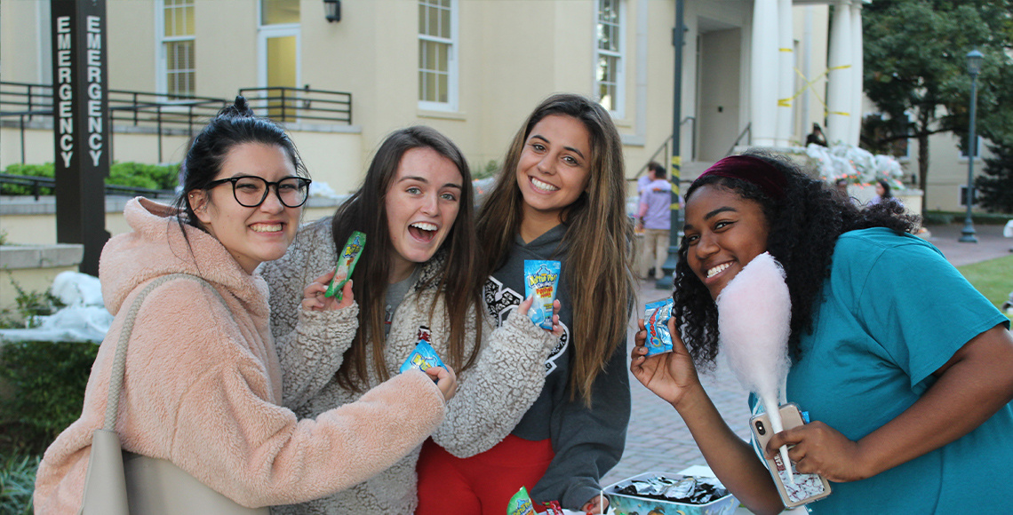Picture of students holding candy at outdoor event