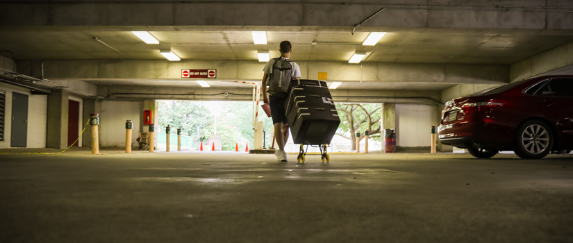 Male student walking in the Bull Street garage pulling luggage on Move-In day