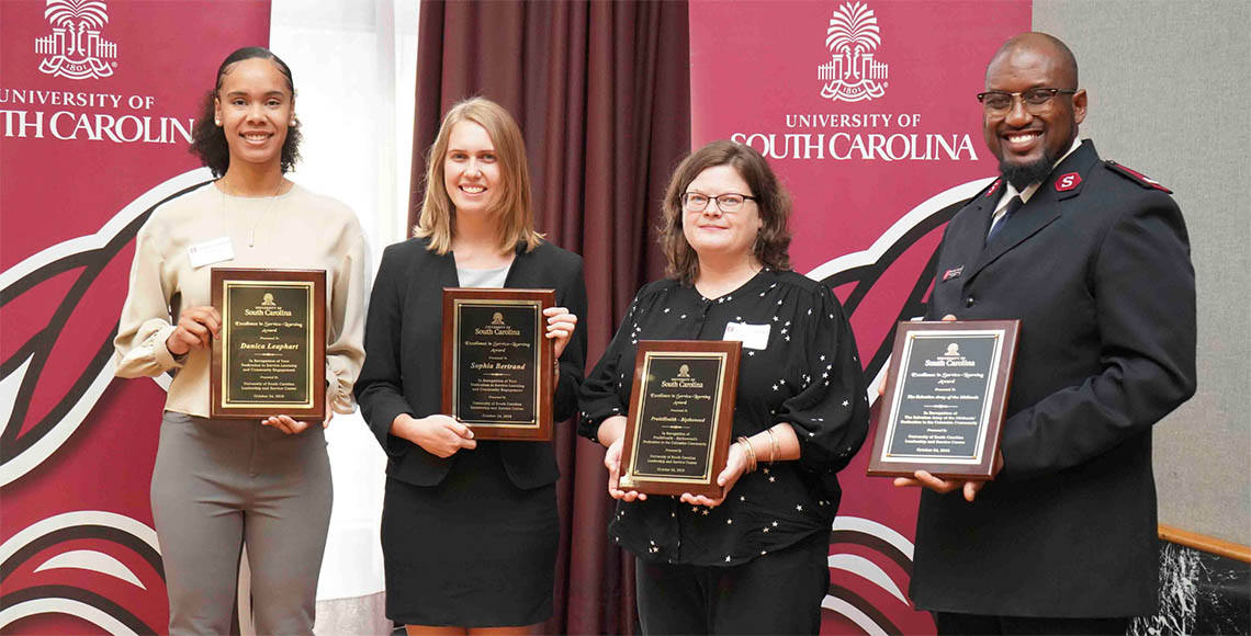 Four people hold award plaques and smile in front of University of South Carolina banners