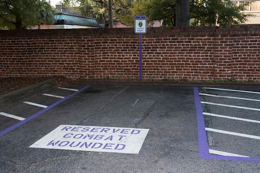 Purple paint and the donated sign designate the new ADA van compliant Purple Heart parking space near the the World War Memorial building on the Columbia campus