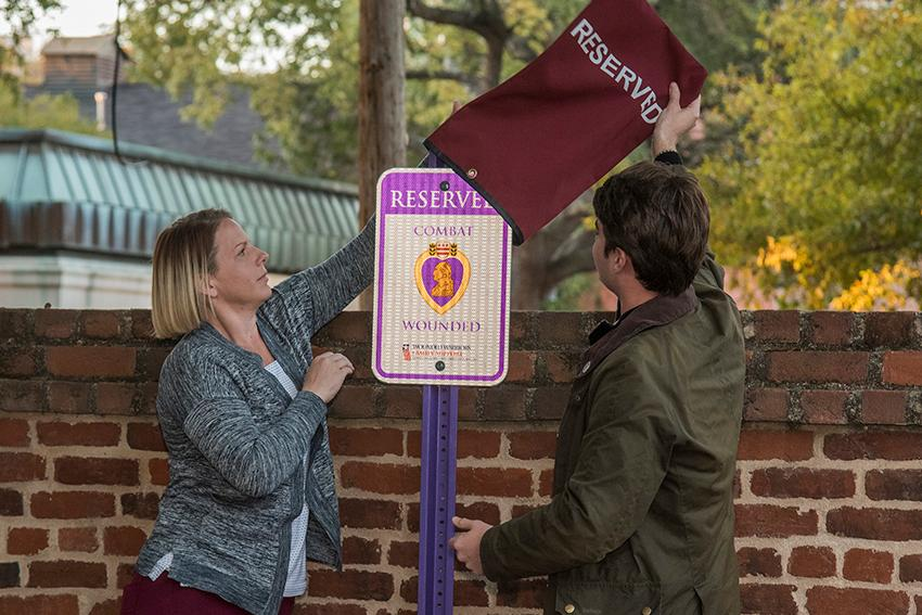 Student Veterans Association president Candace Terry and student body president Luke Rankin unveil the Purple Heart parking space sign that was donated by the South Carolina Department of the Military Order of the Purple Heart.