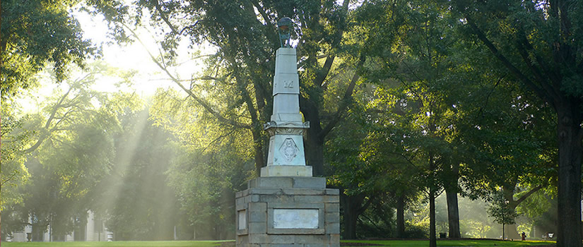 Sunlight filters down through the trees on a monument at the center of the horseshoe