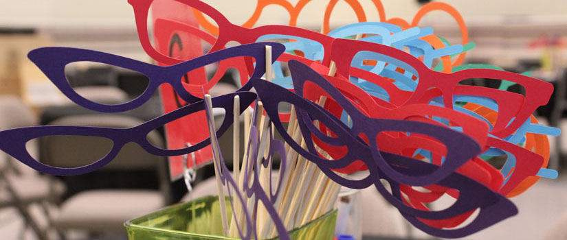 A close up of colorful opera masks shaped like eyeglasses fill a jar