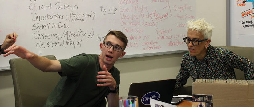 A man and women speak while pointing at a whiteboard