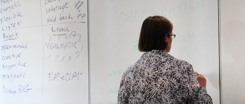 A woman draws on a white board