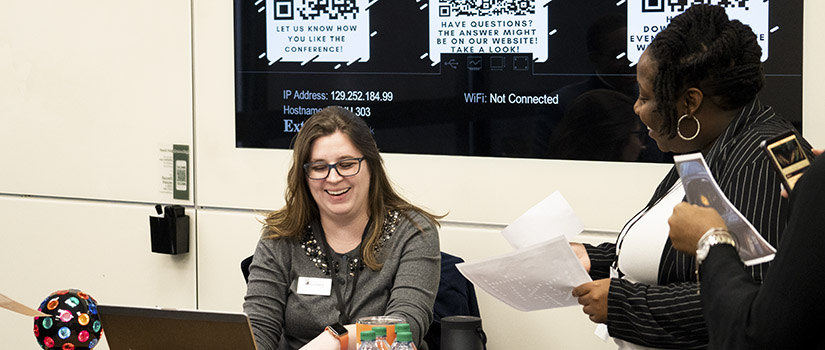 Two women are laughing and looking at a computer with tech walls in the background.