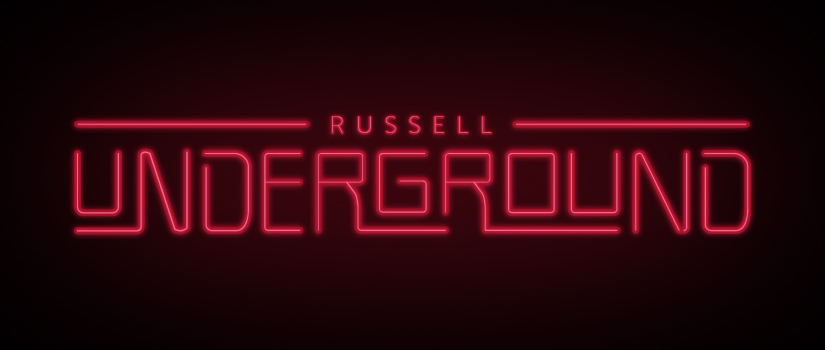"A red neon sign reads ""Russell Underground""."