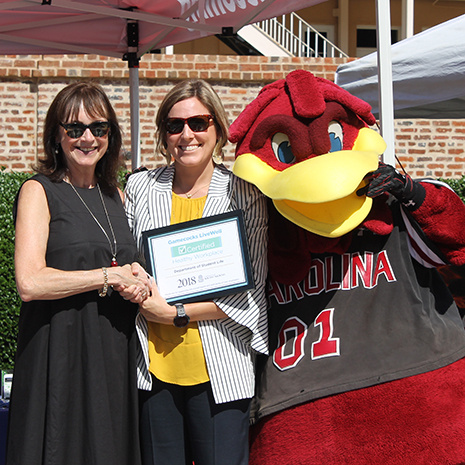 Anna Edwards and Mrs. Pastides with Cocky during the award celebration.