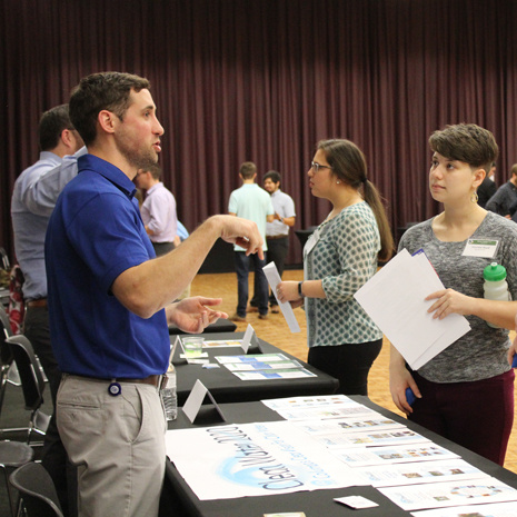 students speaking with an employer at the green career fair