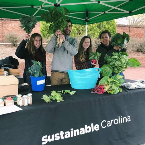 students holding up produce at the farmers market