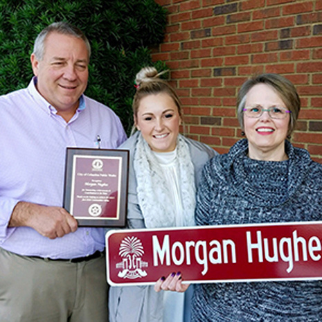 "Morgan Hughes with two community members receiving ""Morgan Hughes Street"" sign and an award for her hard work"