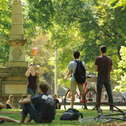 students hanging out on the horseshoe next to the maxcy monument with their bikes and a ball