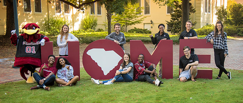 "group of students posing in front of ""HOME"" letters"