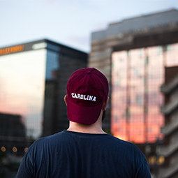 student wearing backwards carolina hat gazing at the sunset