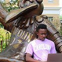 thumbnail image of student sitting by cocky statue
