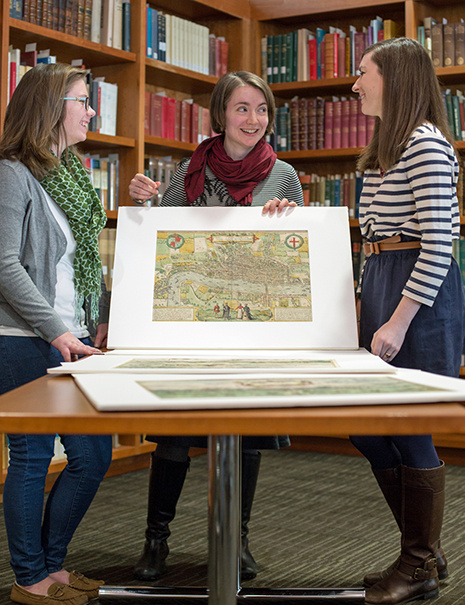 Professor Jeanne Britton shows two students maps from the John and Mary Osman Braun and Hogenberg Collection