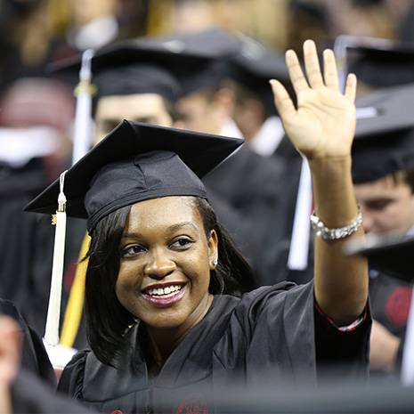 student at graduation waving
