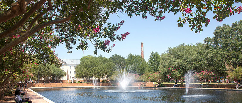 Three fountains in a reflecting pool surrounded by benches with a view of campus and the USC smokestack in the background and a canopy of flowering trees in foreground on a sunny day.