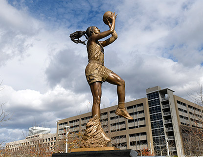 Bronze statue of A'Ja Wilson shooting a basketball with a blue sky in the backgroud.