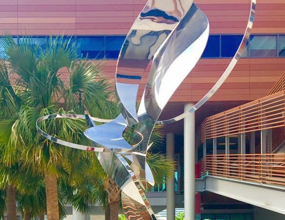 Metal sculpture in the Darla Moore School of Business courtyard surrounded by palmetto trees.