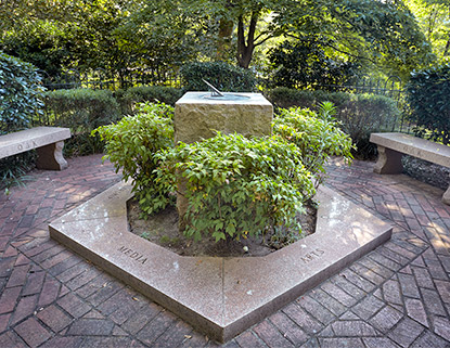 Stone sundial surrounded by bushes and brick pathways just off the historic Horseshoe.