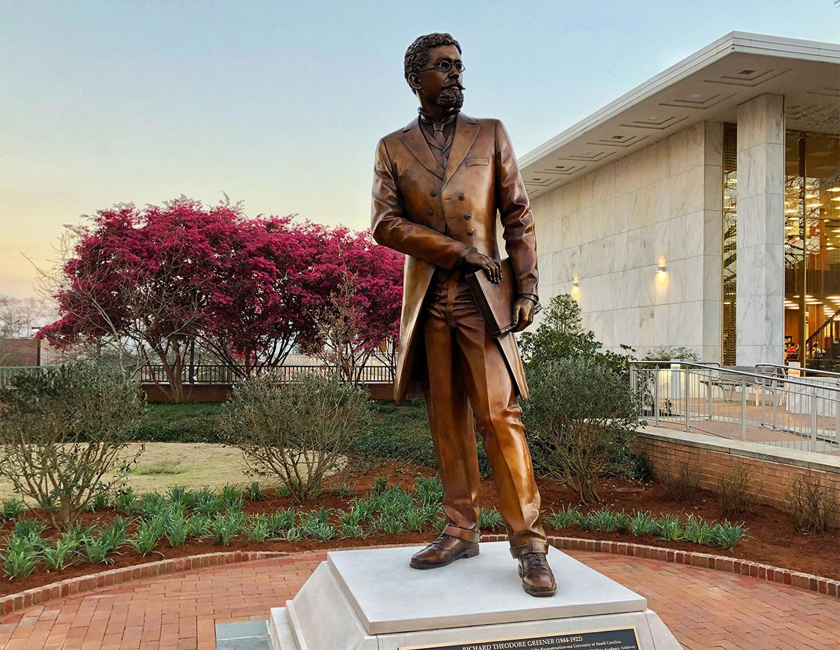 Statue of Richard T. Greener, the first African-American professor at the University of South Carolina, with pink flowers blooming and a sunset in the background.